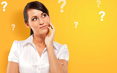Woman inquisitively looking at question marks, weighing her debt management options.