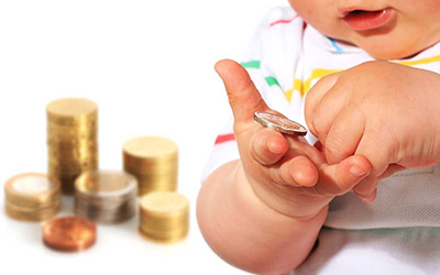 An infant playing with money.