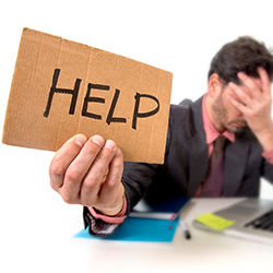 A man depressed about debt holding a HELP sign. Click for articles and videos about financial crisis.