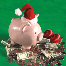 A piggy bank with a christmas hat standing on money. Click for articles and videos about holiday spending.
