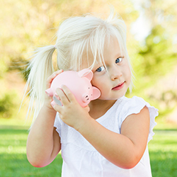 A young girl with a piggy bank. Click for articles and videos about kids and money.