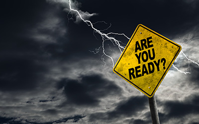 Image of a sign in front of storm clouds that reads 'are you ready' for a disaster