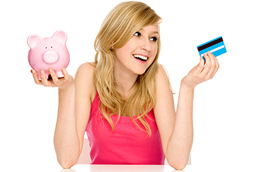 A teenage girl holding a piggy bank and a credit card.