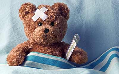A teddy bear in bed with a bandage and a thermometer.