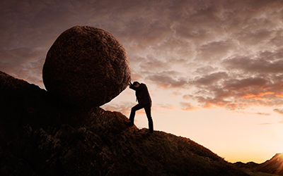 Image of a financially stressed man pushing a boulder up a hill.