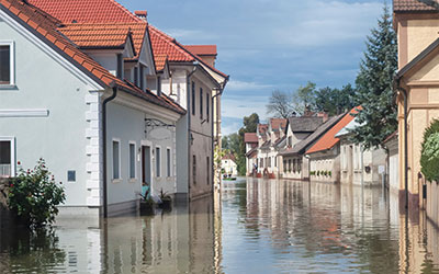 A city street and homes buried in water caused by a flood.