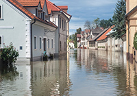Image of houses with water up to the windows caused by a flood. Click to learn more about preparing for a flood.