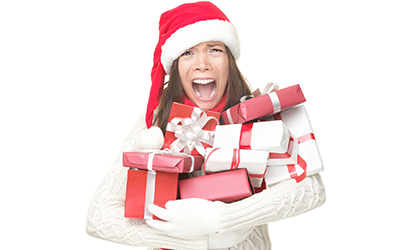 A stressed-out woman holding a stack of holiday gifts.