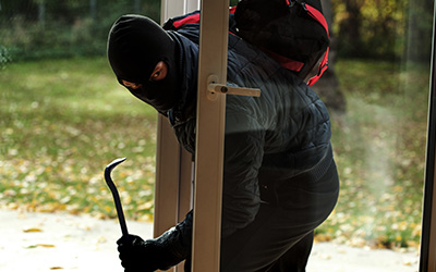 Image of a burglar breaking into a house.