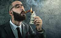 A man with a beard wearing a suit lighting a cigar with cash.