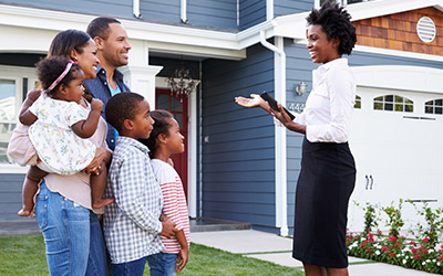 A female real estate agent showing a home to a young family.