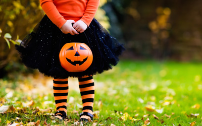 A little girl standing outside and wearing orange and black holding a pumpkin bucket.