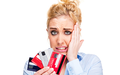 Confused woman holding several credit cards.