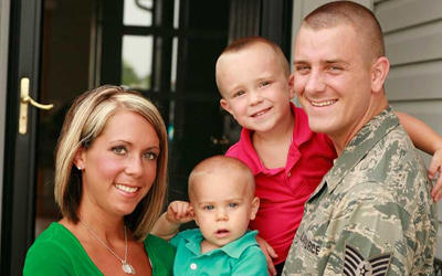 A military service member, his wife and two children.
