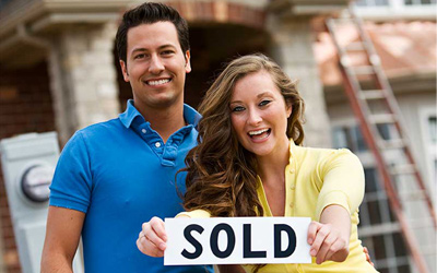 A young couple standing in front of a home. The female is holding a sign that says sold.