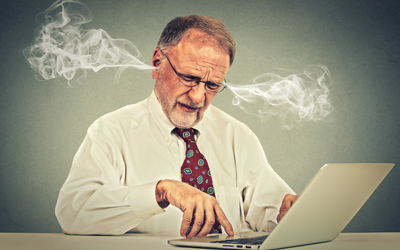 A middle-aged man on his computer with smoke coming from his ears.
