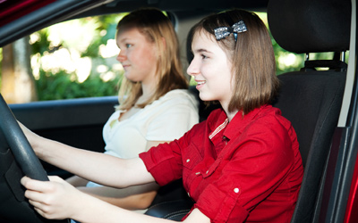 A teenage girl driving with her mother in the passanger seat.