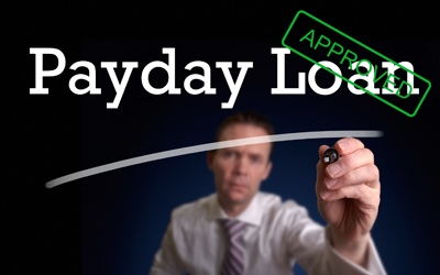 Image of a man writing the words PAYDAY LOAN on the screen.