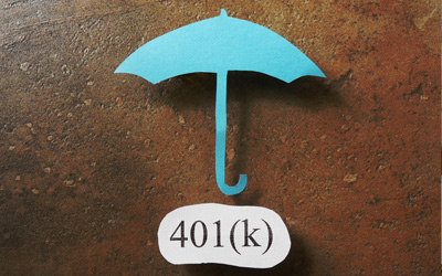 An umbrella over a piece of paper with 401k typed onto it.